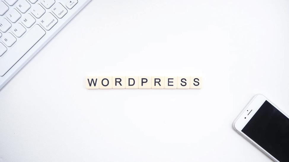 WordPress logo with phone and keyboard